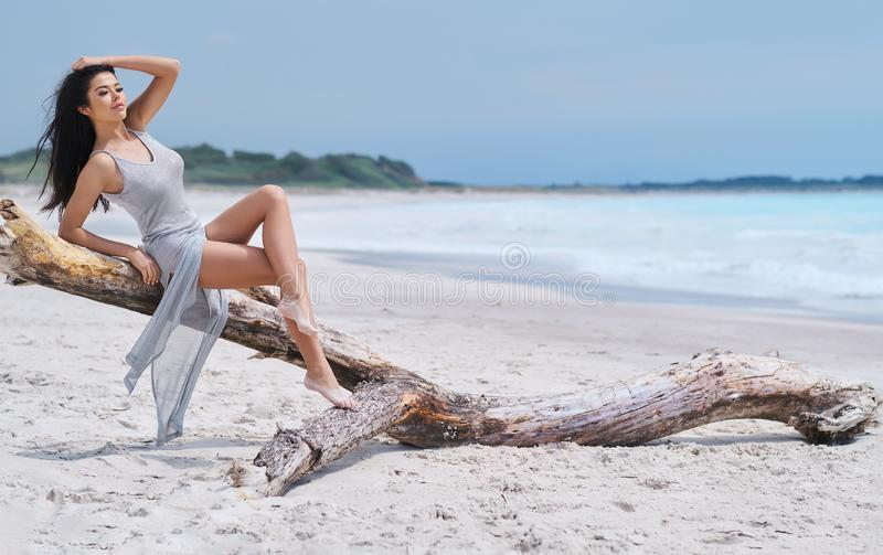 Beautiful young woman in elegant dress on the beach royalty free stock photo