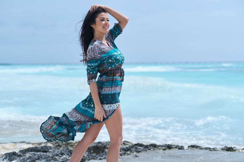 Beautiful young woman in elegant dress on the beach royalty free stock photography