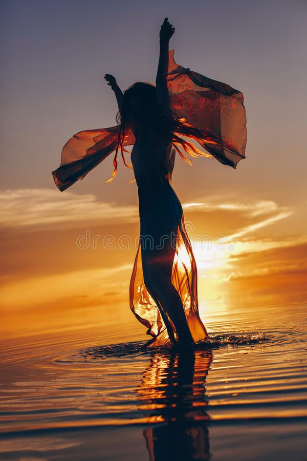 beautiful young woman in elegant dress walking on water at sunset stock image