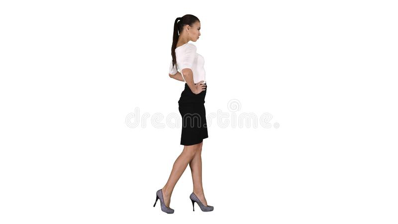 Beautiful young woman in elegant outfit walking, holding hands on hips on white background. stock image