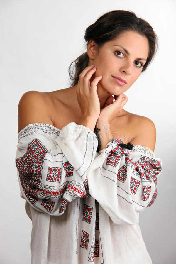 Beautiful young woman in embroided chemise. Portrait of beautiful young woman in embroided chemise royalty free stock photo