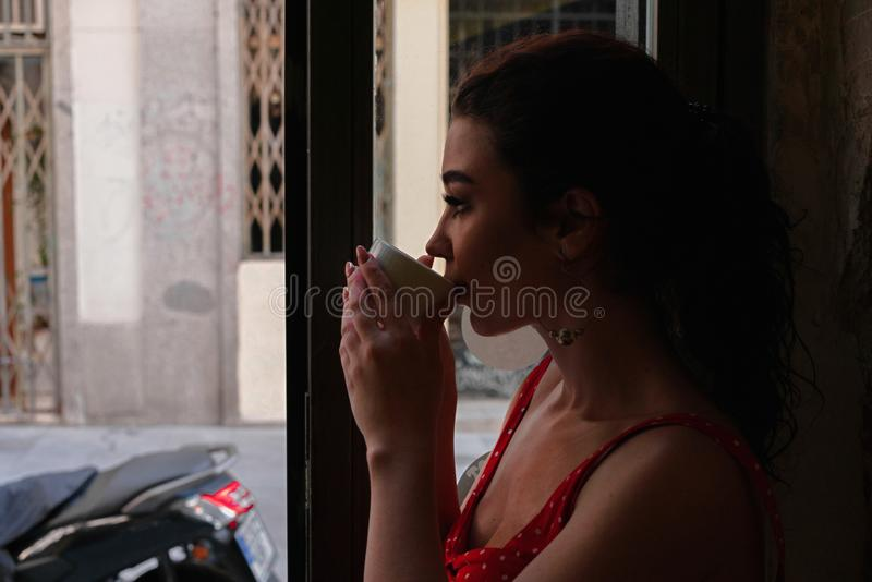 Beautiful young woman enjoying coffe cup and looking at street of European old town at morning time stock photos