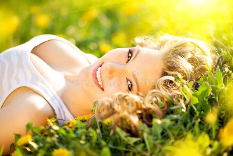 Beautiful young woman enjoying nature. Beautiful young woman lying on a field enjoying nature stock images