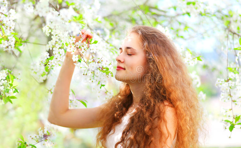 Beautiful young woman enjoys smell spring flowers over garden. Background royalty free stock photography