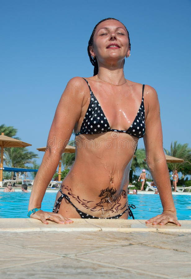Beautiful young woman enters the pool stock images