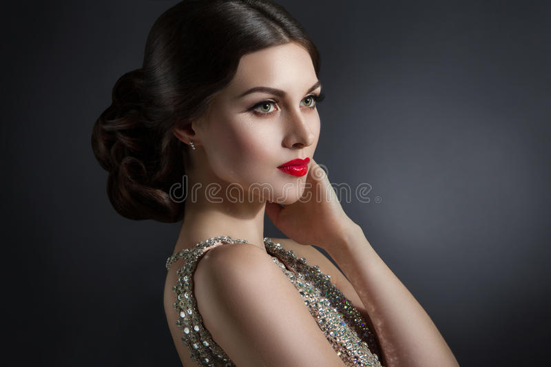 Beautiful young woman in an evening dress crystal. Perfect beauty, red lips, bright makeup. Twinkling sparkling stones on dress royalty free stock photos