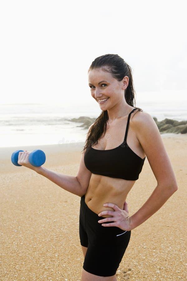 Beautiful young woman exercising on beach stock photos