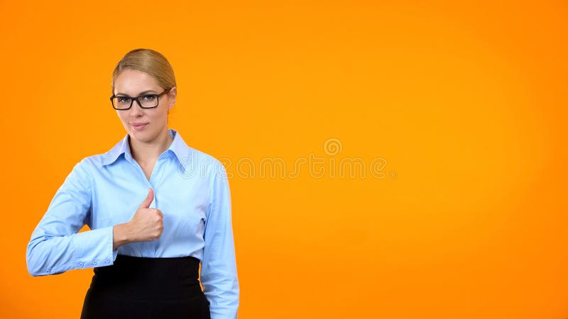 Beautiful young woman in eyeglasses showing thumbs up on orange background royalty free stock photo