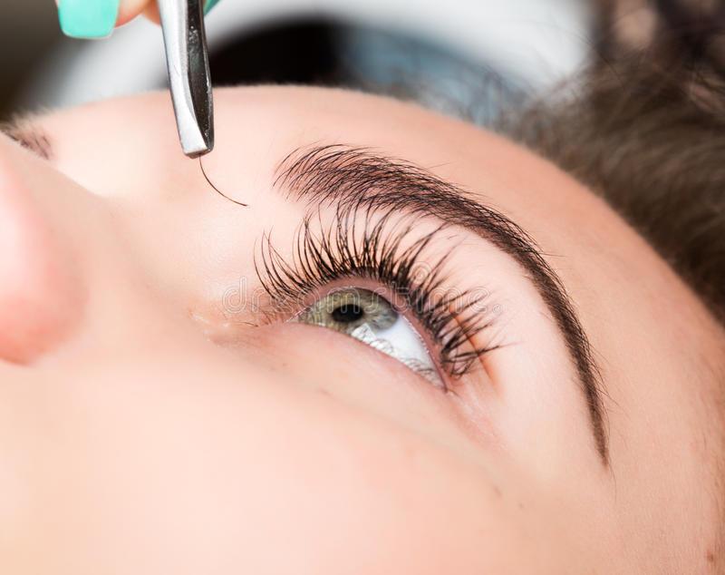 Beautiful young woman eyelash extension. Woman eye with long eyelashes. Beauty salon concept royalty free stock photos