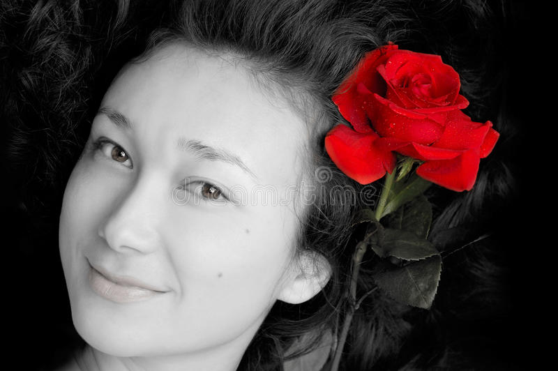 Beautiful young woman face. With a red rose in her hair stock photography