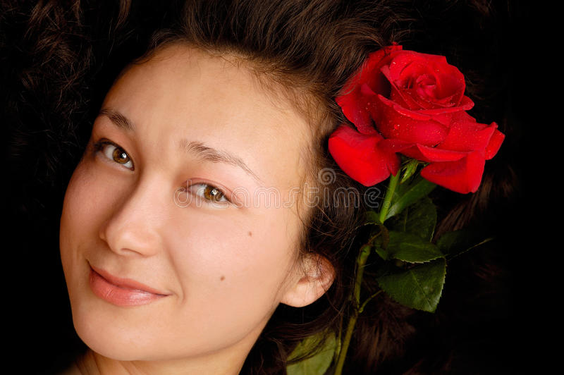 Beautiful young woman face. With a red rose in her hair royalty free stock image