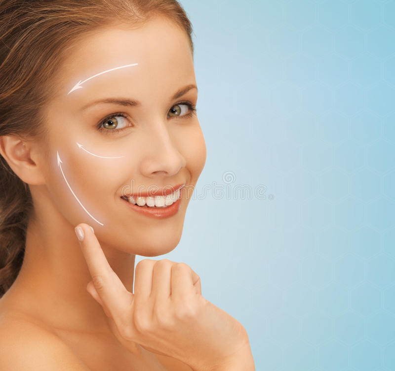 Beautiful young woman face. Beauty, plastic surgery, anti-aging, people and health concept - beautiful young woman applying creme to her face with lifting arrows stock photography
