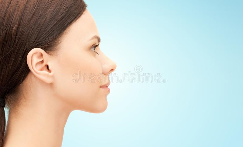 Beautiful young woman face over blue background royalty free stock image
