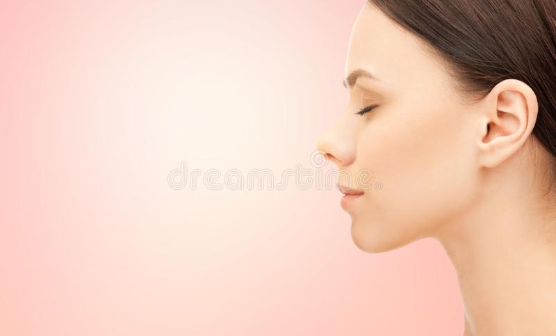 Beautiful young woman face over pink background stock photo