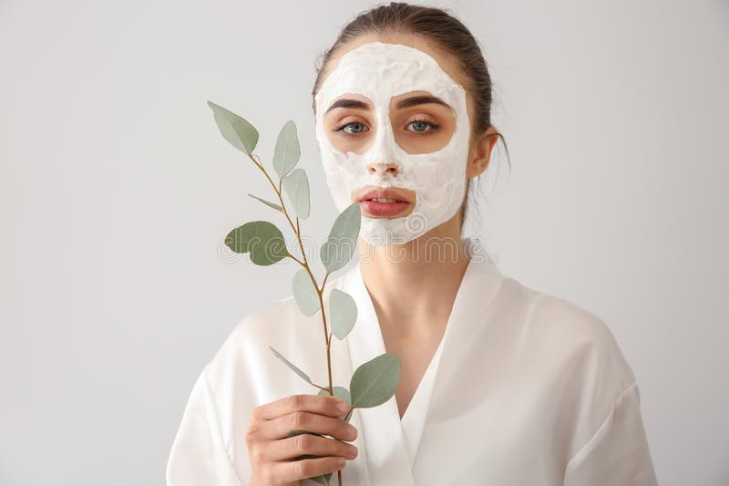Beautiful young woman with facial mask and eucalyptus branch on light background royalty free stock image