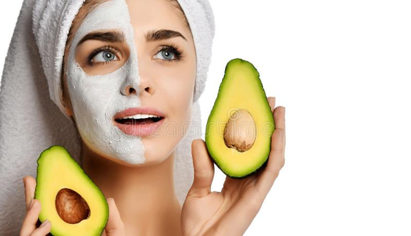 Beautiful young woman with facial mask and fresh avocado on white background. Beauty skin care. Concept royalty free stock photos