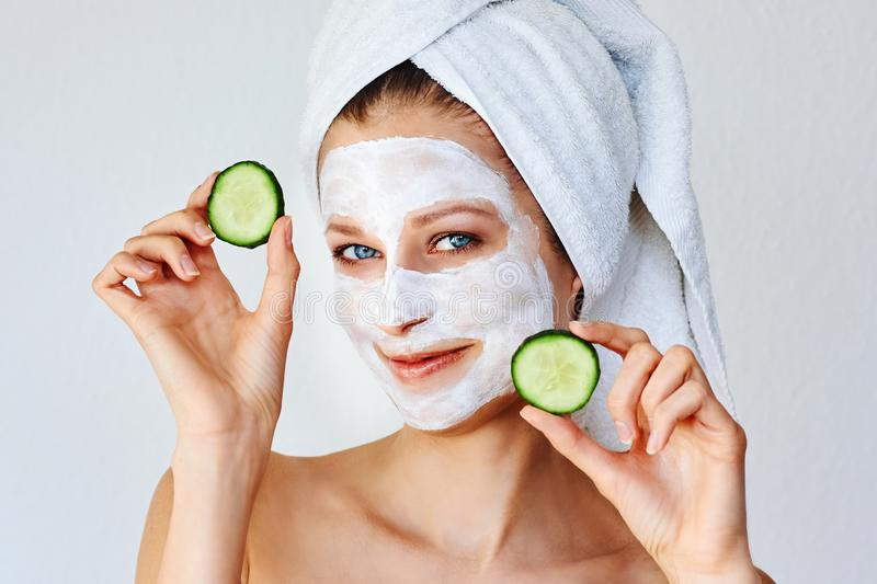 Beautiful young woman with facial mask on her face holding slices of cucumber. Skin care and treatment, spa and cosmetology stock photos