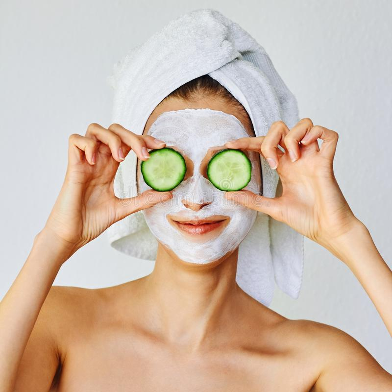Beautiful young woman with facial mask on her face holding slices of cucumber. Skin care and treatment, spa and cosmetology royalty free stock image