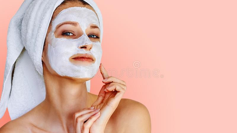 Beautiful young woman with facial mask on her face. Skin care and treatment, spa, natural beauty and cosmetology concept royalty free stock photography