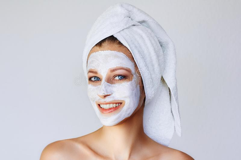 Beautiful young woman with facial mask on her face. Skin care and treatment, spa, natural beauty and cosmetology concept stock image