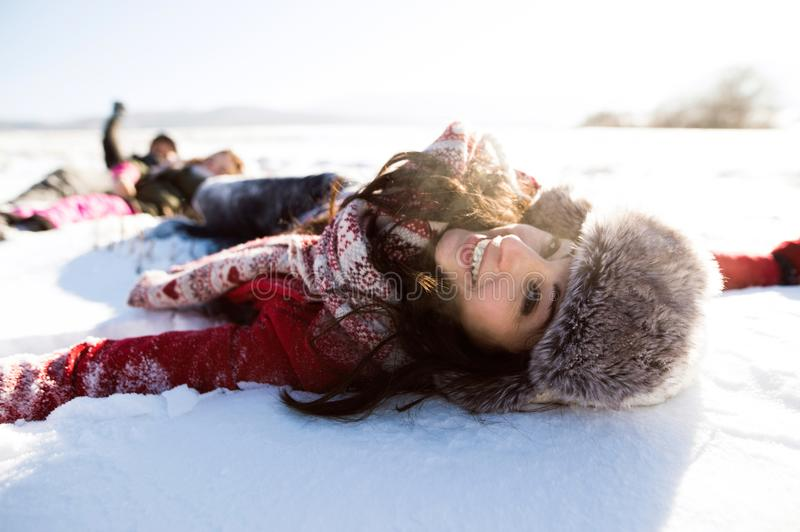 Beautiful young woman with family, having fun in the snow. stock photos