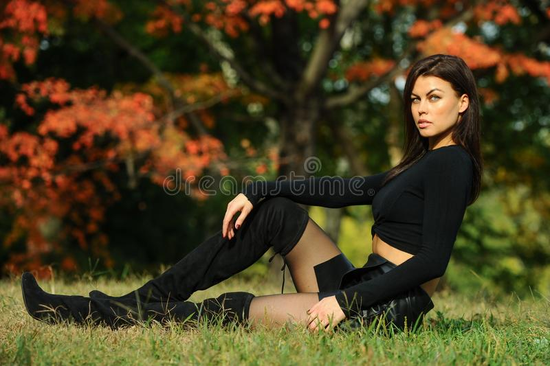 Beautiful young woman in fashionable black clothes sitting in the park. With autumn trees on the background stock images