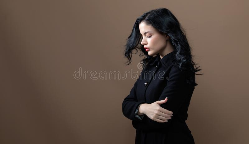 Beautiful young woman in a fashionable coat. On a brown background stock image