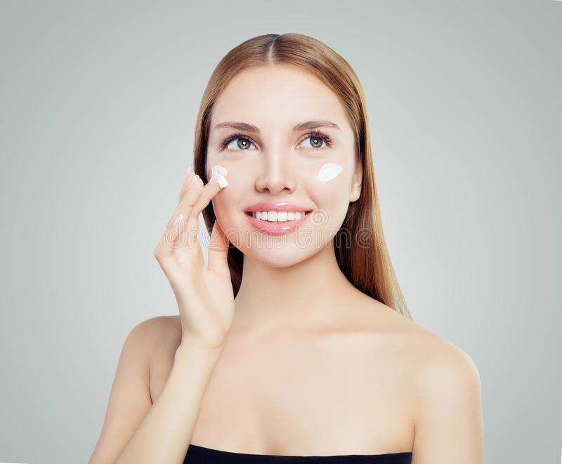 Beautiful young woman female model applying cosmetic cream treatment on her face on white background stock photo