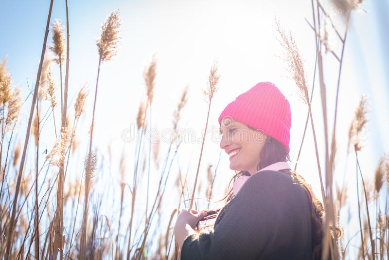Beautiful Young Woman in a Field of High Grass Listening Music royalty free stock image