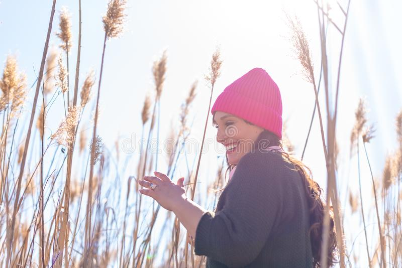 Beautiful Young Woman in a Field of High Grass Listening Music stock image