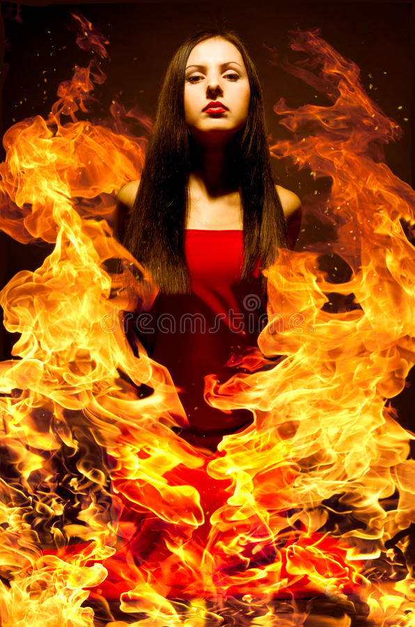 Beautiful young woman on fire. Portrait of a beautiful young woman on fire royalty free stock photography