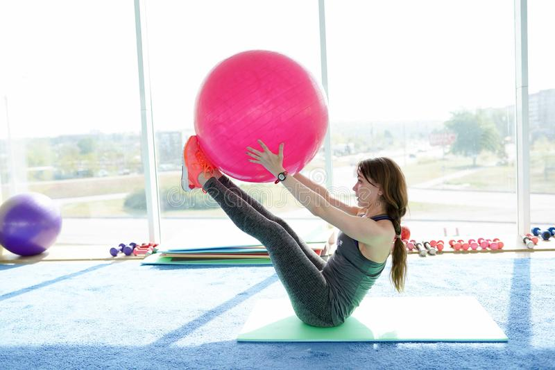Beautiful young woman with fitness ball training in gym . concept of healthy lifestyle.  royalty free stock photos