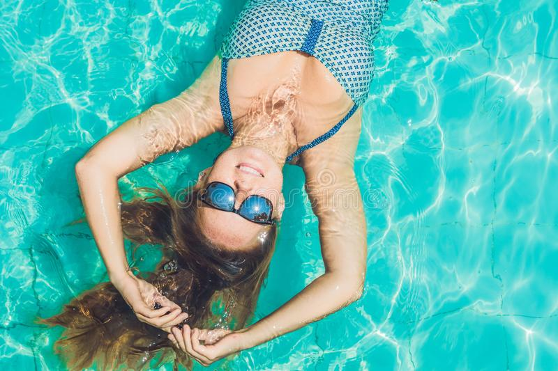 Beautiful young woman floating in pool relaxing Top view. Holiday concept stock photography