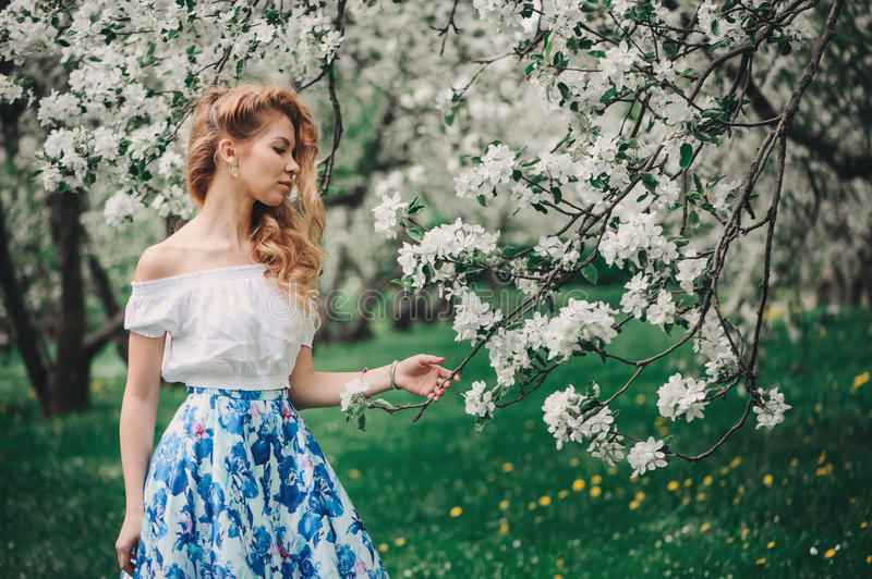 Beautiful young woman in floral maxi skirt walking in blooming spring garden stock photography