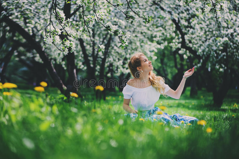 Beautiful young woman in floral maxi skirt walking in spring stock photo
