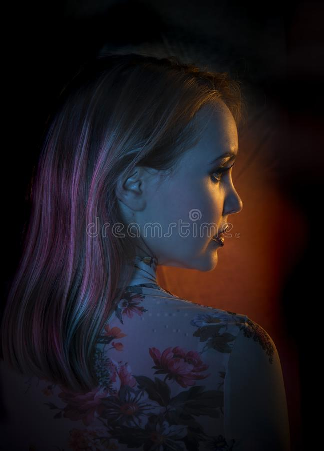Beautiful young woman with floral patterned shirt posing in creative pink, blue and orange light in front of a black background royalty free stock photo