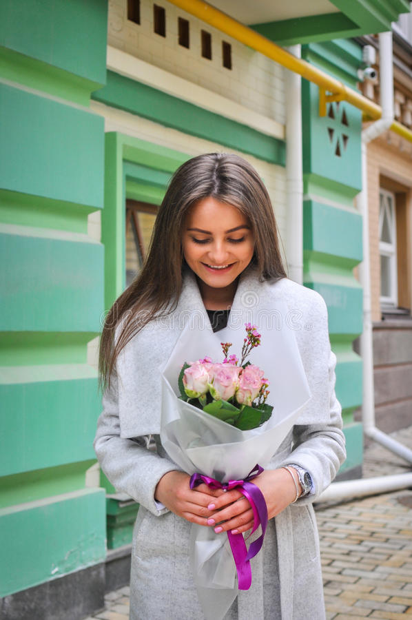 Beautiful young woman with flowers bouquet at city street. Spring portrait of pretty female.  stock images