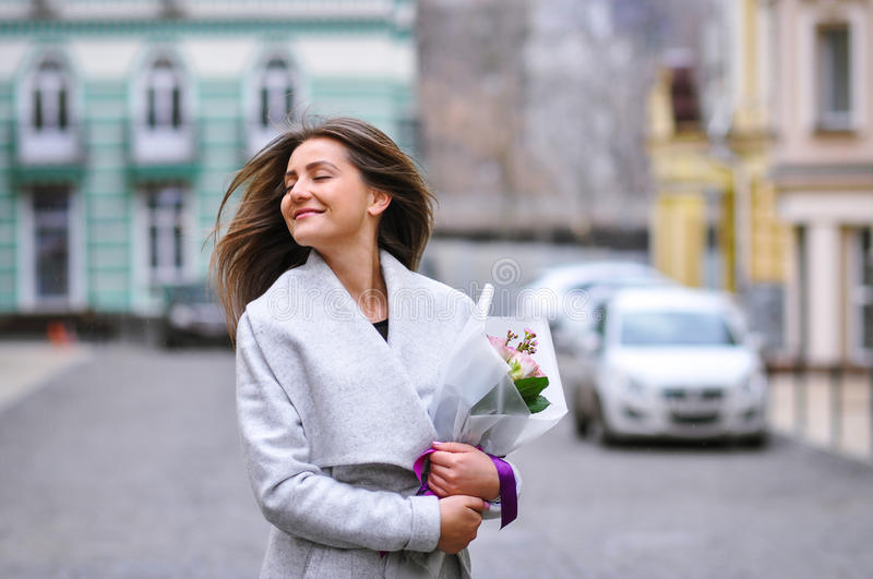Beautiful young woman with flowers bouquet at city street. Spring portrait of pretty female.  stock photo