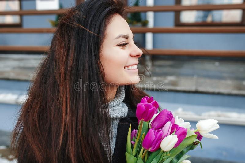 Beautiful young woman with flowers outdoor portrait, spring girl hold fresh bouquet, fashionable elegant lady at city. Spring woman with flowers in city street royalty free stock images