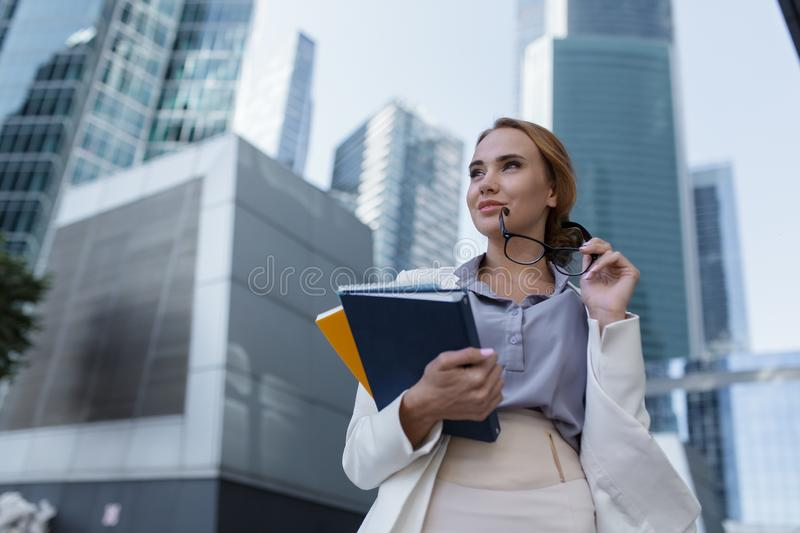 Beautiful young woman with folders and documents in her hands standing among the skyscrapers of the modern business center. Young woman with folders and royalty free stock photo