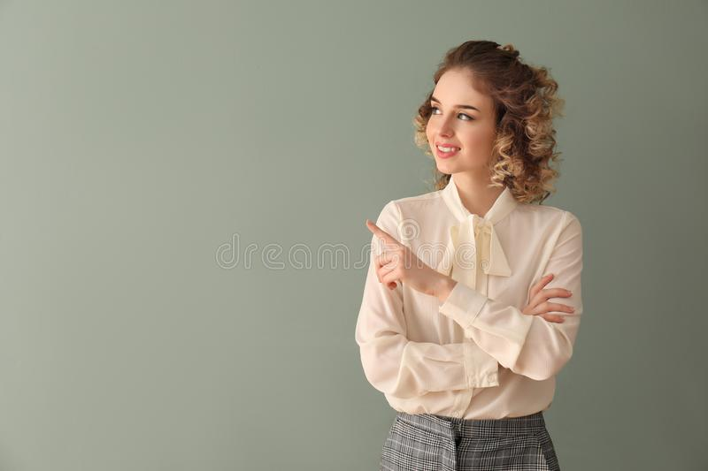 Beautiful young woman in formal clothes pointing at something on color background stock image