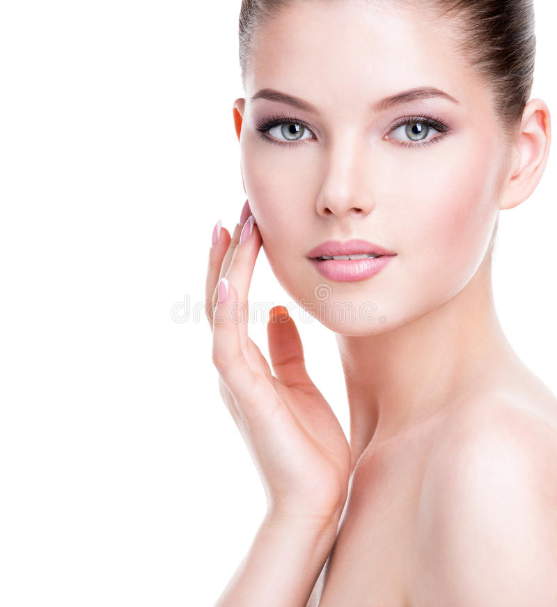 Beautiful young woman with fresh clean skin. Beautiful young woman with fresh clean skin that touches her face with a hand - isolated on white stock photography