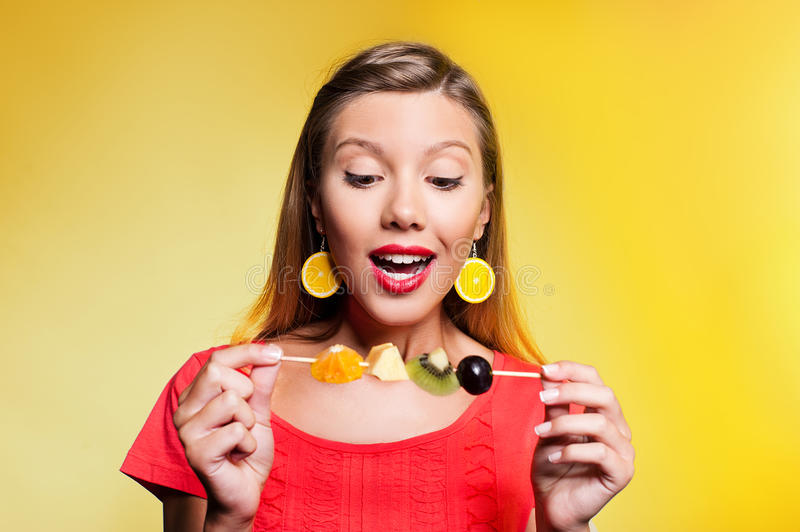 Beautiful young woman with fruit skewer royalty free stock photo
