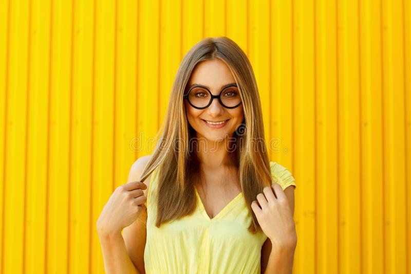 Beautiful young woman in funny toy glasses smiling over yellow b stock photography