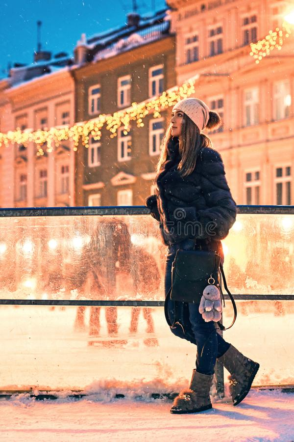 Beautiful young woman in fur coat stands by a skating rink border on old snowy European city background stock photos