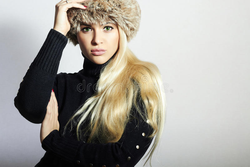 Beautiful Young Woman in Fur Hat. Pretty Blond Girl. Winter Fashion Beauty. Healthy hair royalty free stock photo