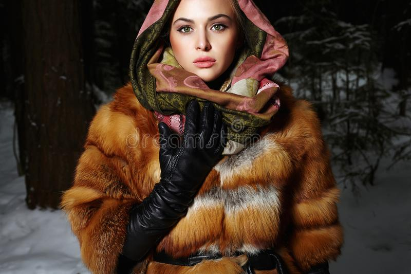 Beautiful young Woman in Fur and scarf. At night in winter forest. winter style girl royalty free stock image