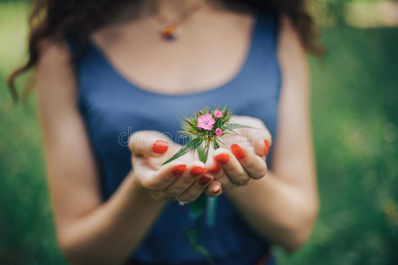 Beautiful young woman, in the garden with blooming trees. Springtime, hands care royalty free stock images