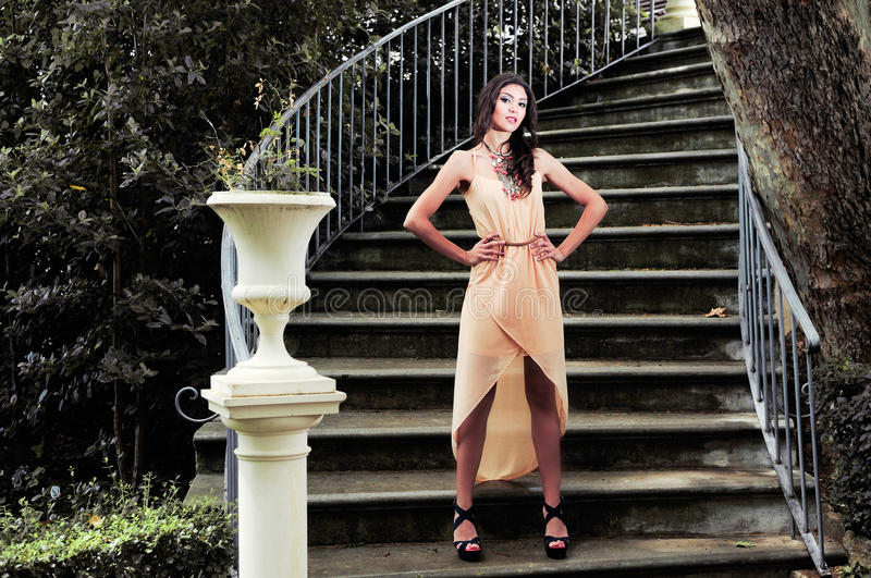 Beautiful young woman in a garden stairs. stock photo