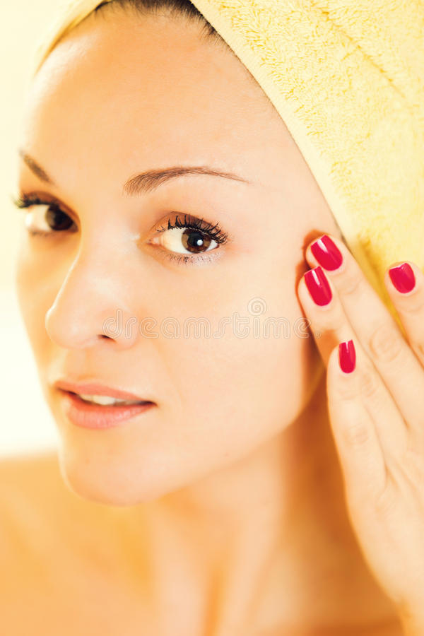 Beautiful young woman gently touching her face stock photo